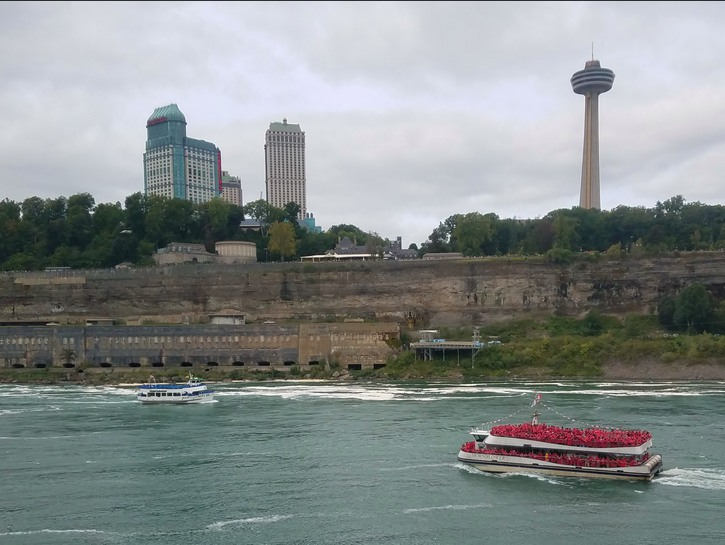 Maid of the Mist sailing down river, with Skylon Tower in the background