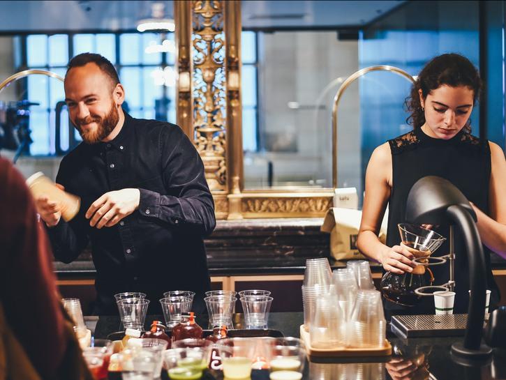 Male and female bartender making drinks behind bar