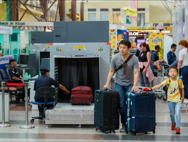 Man and son push suitcases past airport security