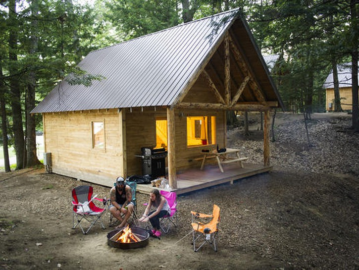 Man and woman have campfire outside wooden cabin in the woods