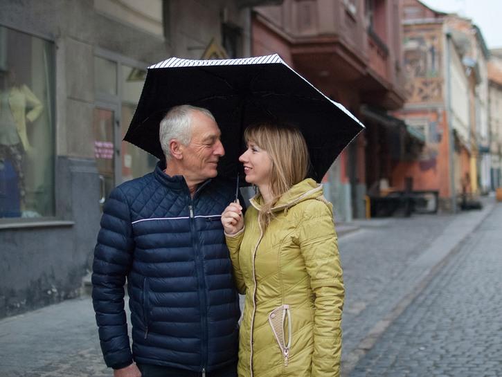 man and woman sharing an umbrella