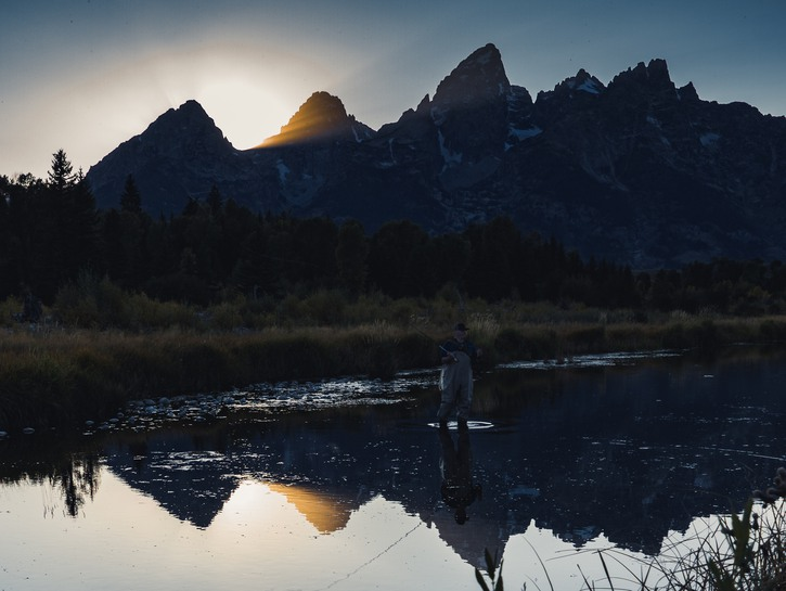 Man fishing in lake under mountains