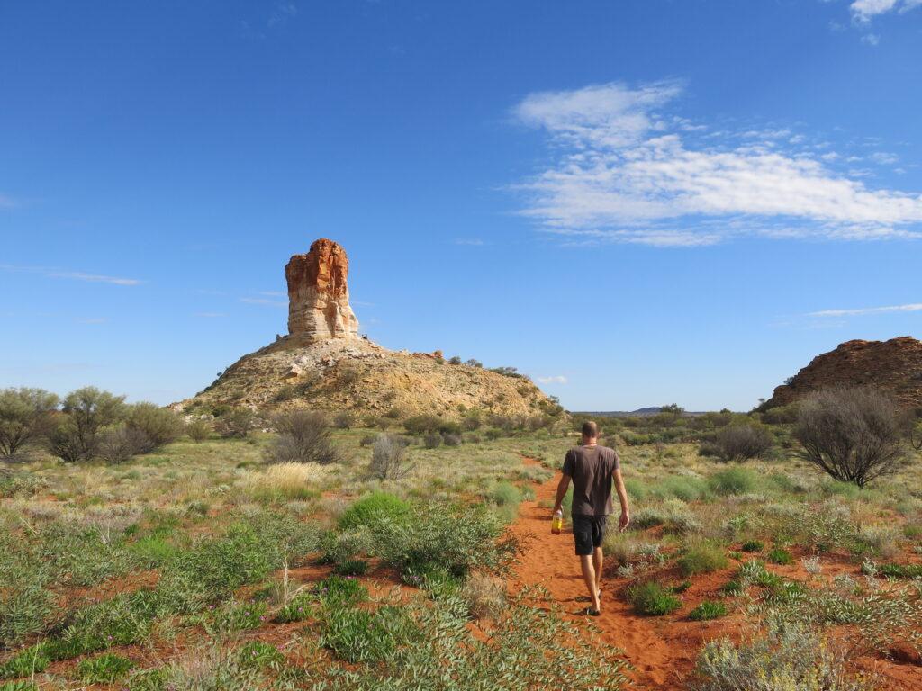 Man hiking toward Chambers Pillar, Northern Territory, Australia