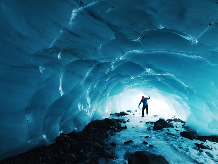 Man in blue glacial cave