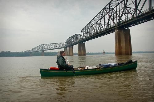 Man in canoe under the old Chain of Rocks Bridge