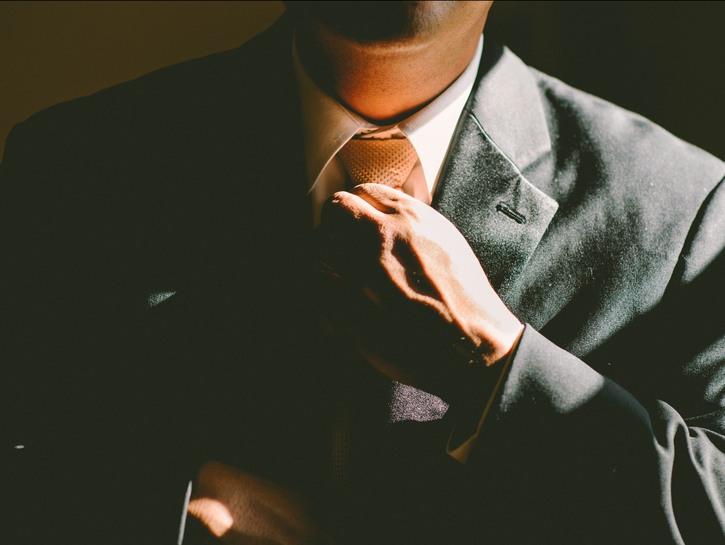 Man in dark grey suit adjusts his tie