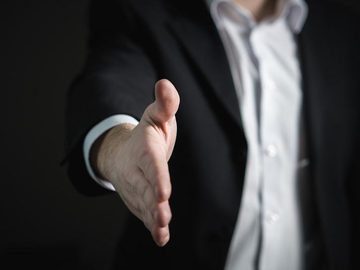 Man in dark suit extends handshake
