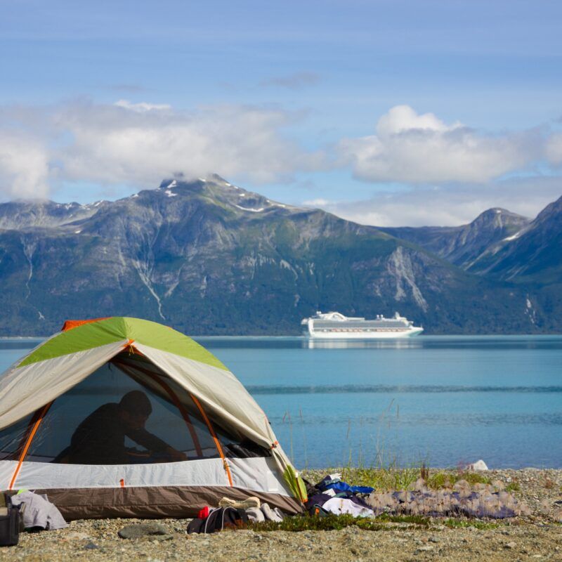 man in tent with lake and mountains in background