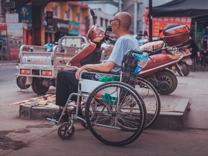 Man in wheelchair on the sidewalk