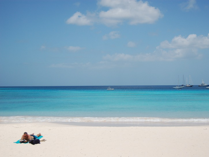 Man laying on beach in Barbados