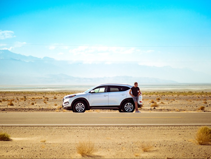 Man leans on his SUV on the side of a desert highway