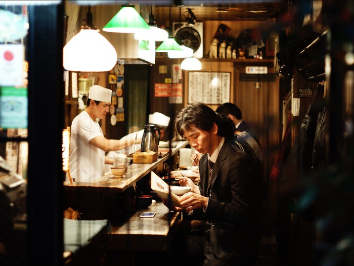man reading at counter in restaurant