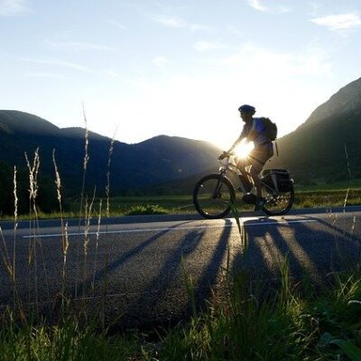 man riding electric bike in front of sunset