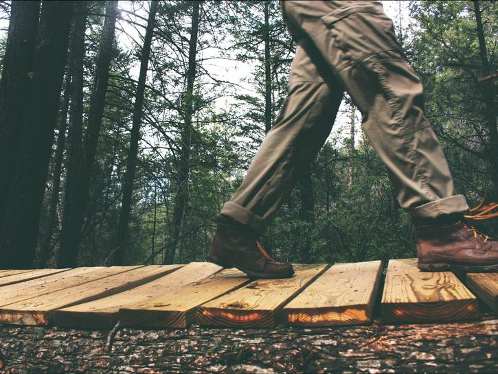 Man's legs walking on boardwalk in forest