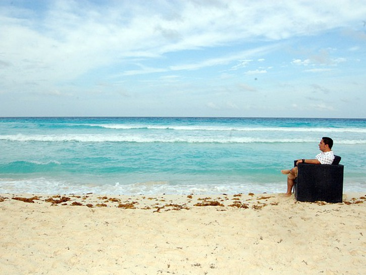 Man sits on couch in the sand on Playa del Carmen beach.