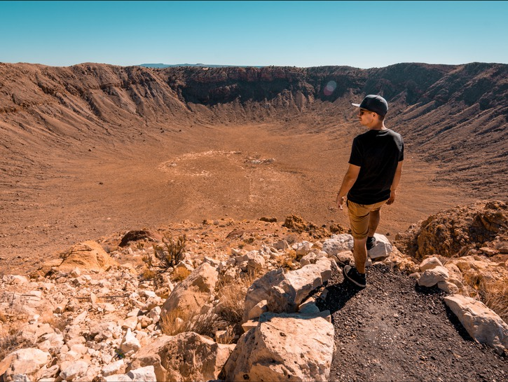 Man stands on a rock overlooking Meteor Crater, Arizona
