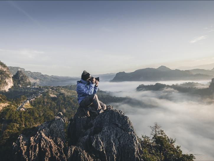 Man taking picture on mountain