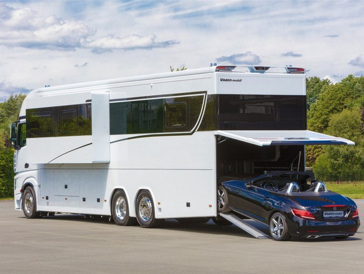 Mercedes Vario Alkoven 1200 RV with sports car driving into its rear garage compartment.