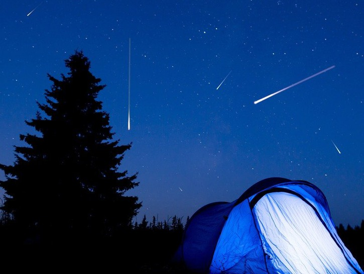Meteors in the night sky behind an illuminated blue tent
