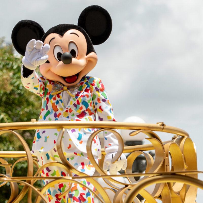 Mickey Mouse waving to visitors at the Magic Kingdom.