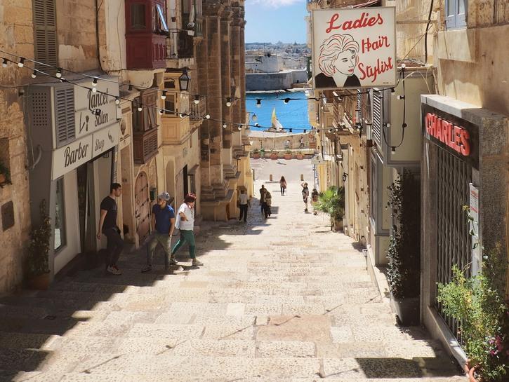 Narrow avenue of the Maltese capital, Valetta, winding toward a hint of the Mediterranean.