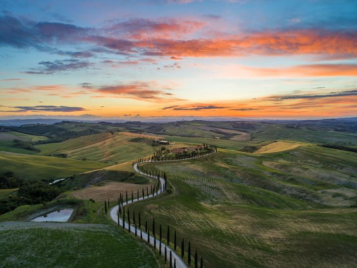 Narrow lane leading through the hills of Tuscany toward a farmhouse at sunset