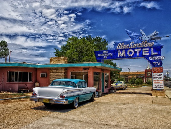 Old 70s car parked in front of old motel