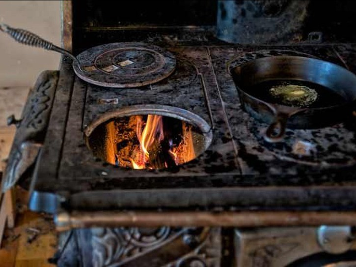 Old early 1900s stovetop with fire at Hillside Homestead