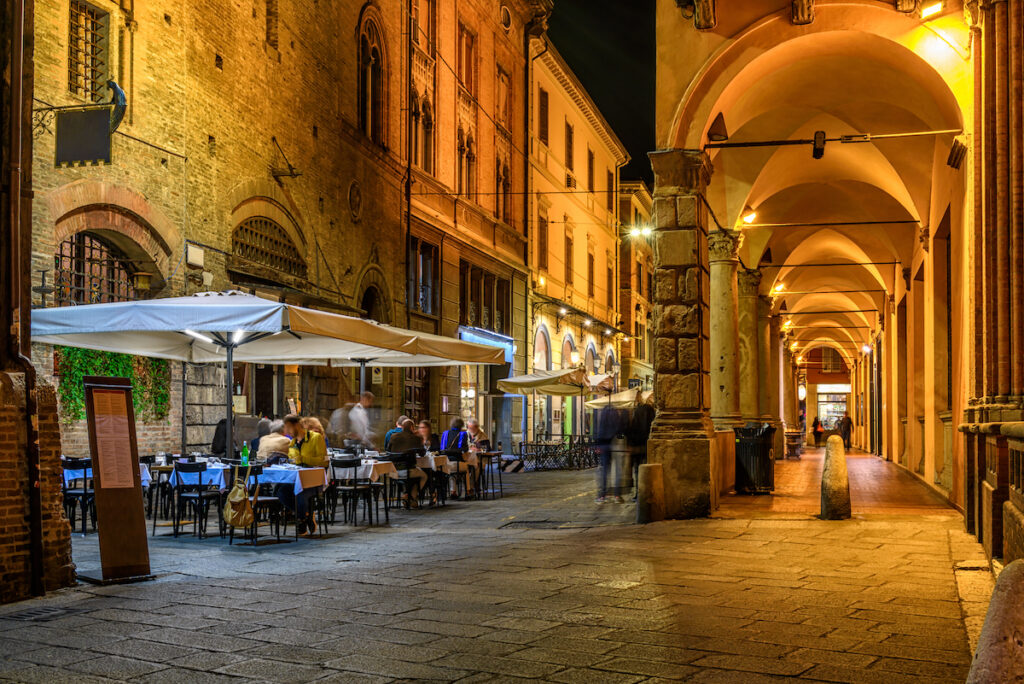 Old narrow street with outdoor restaurant in Bologna, Italy.