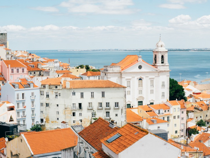Old white buildings with ocean in background, Lisbon, Portugal