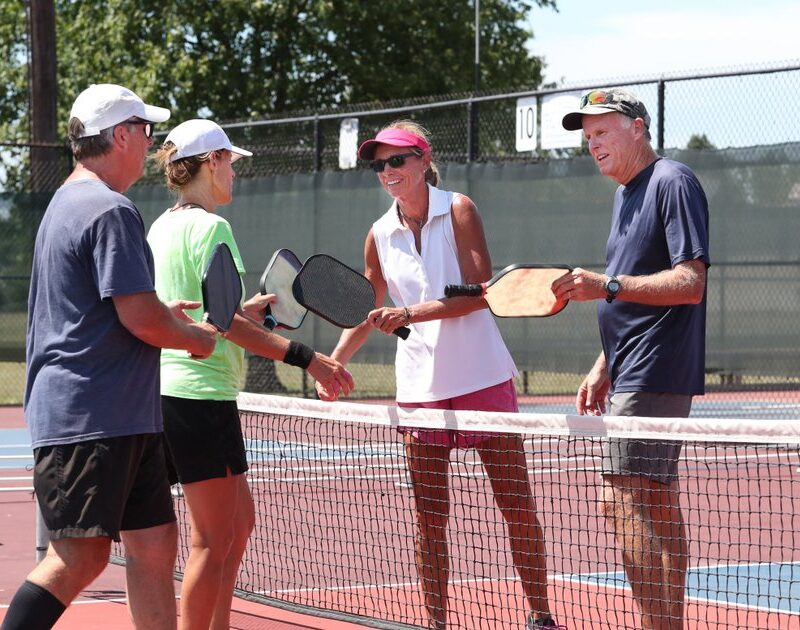 Older adults playing pickleball outside.