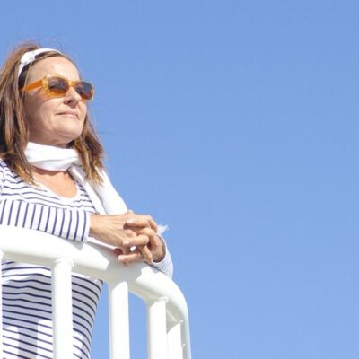 older woman with sunglasses gazes out from balcony