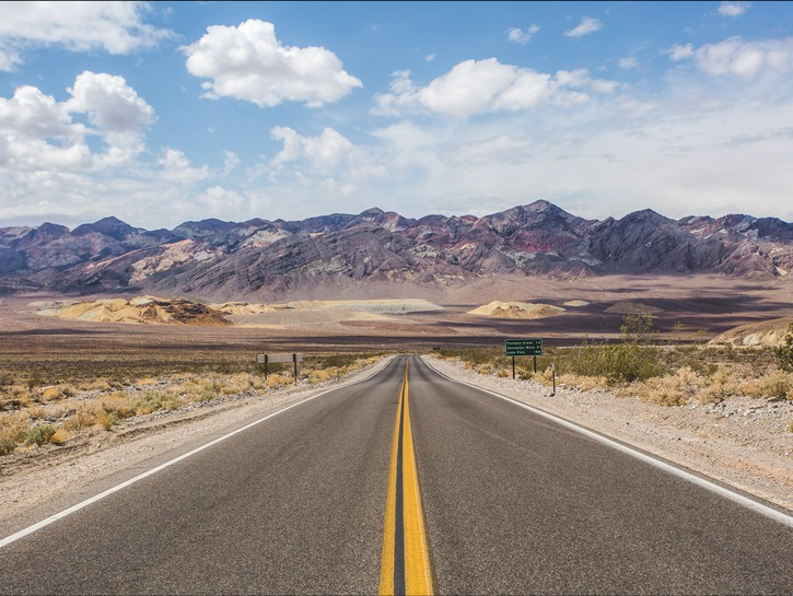Open road in the desert, mountains in the background