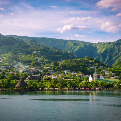 Papeete, Tahiti, shoreline with buildings and lush vegetation.