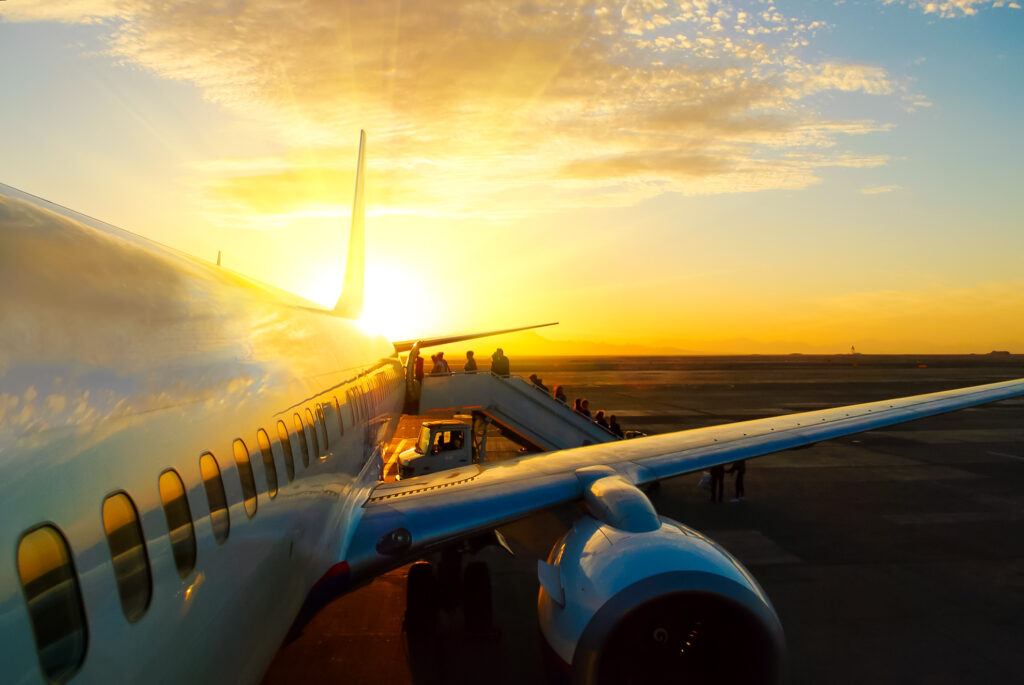 Passengers boarding an airplane at sunrise