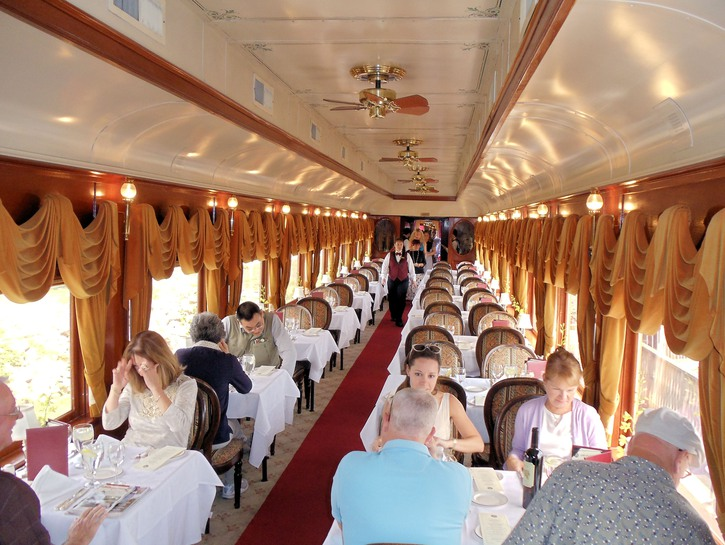 Passengers seated at tables aboard Napa Valley wine train.