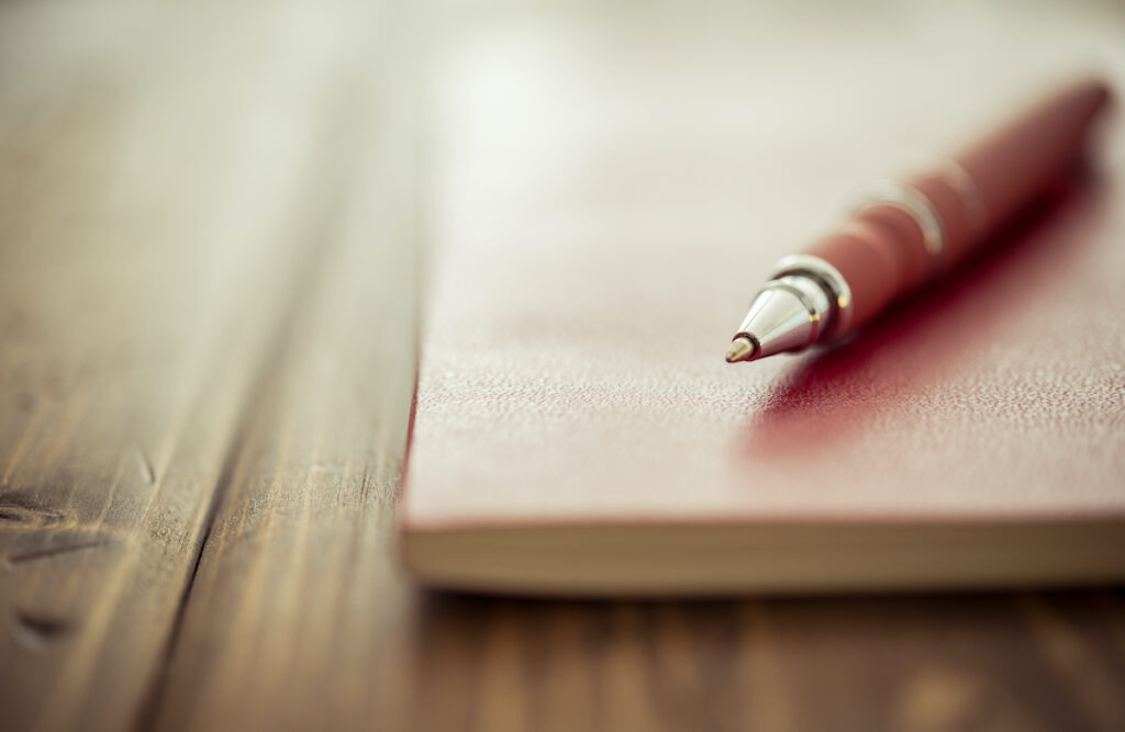 Pen and journal on wooden desk.