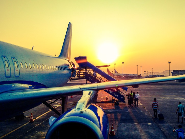People board airplane on the tarmac, sunset in the background