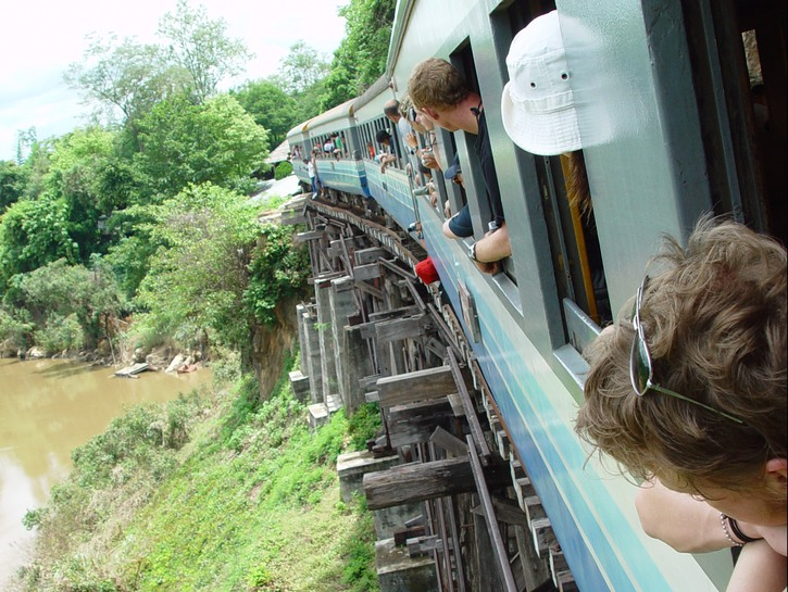 People hang out windows on Death Railway, Thailand