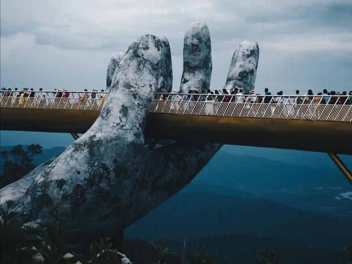 People walk across Golden Bridge in Ba Na Hills, Vietnam, on a cloudy day