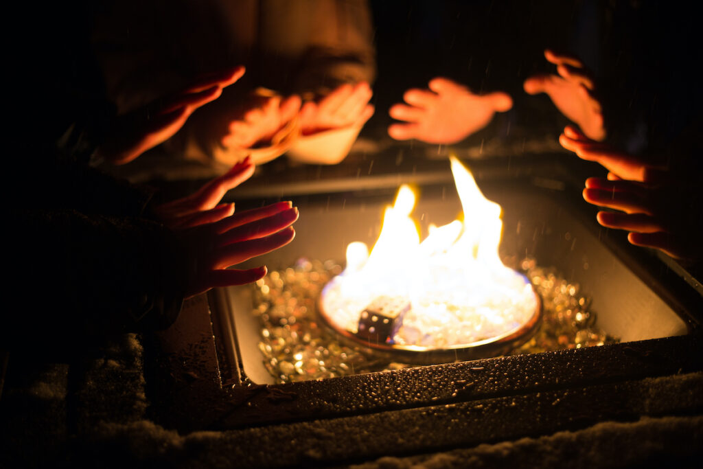People warming their hands by the fire at the New Hampshire Ice Castles.