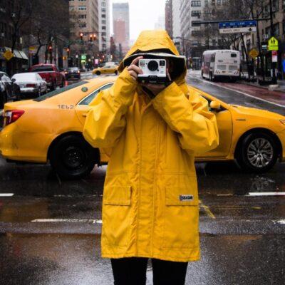 person in raincoat taking photo