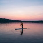 person on stand up paddle board on lake