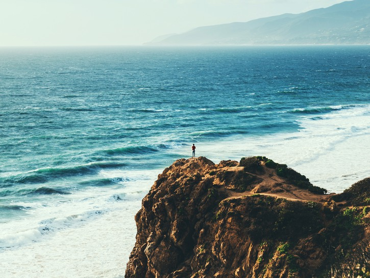 Person standing on rock of Point Dume, Malibu
