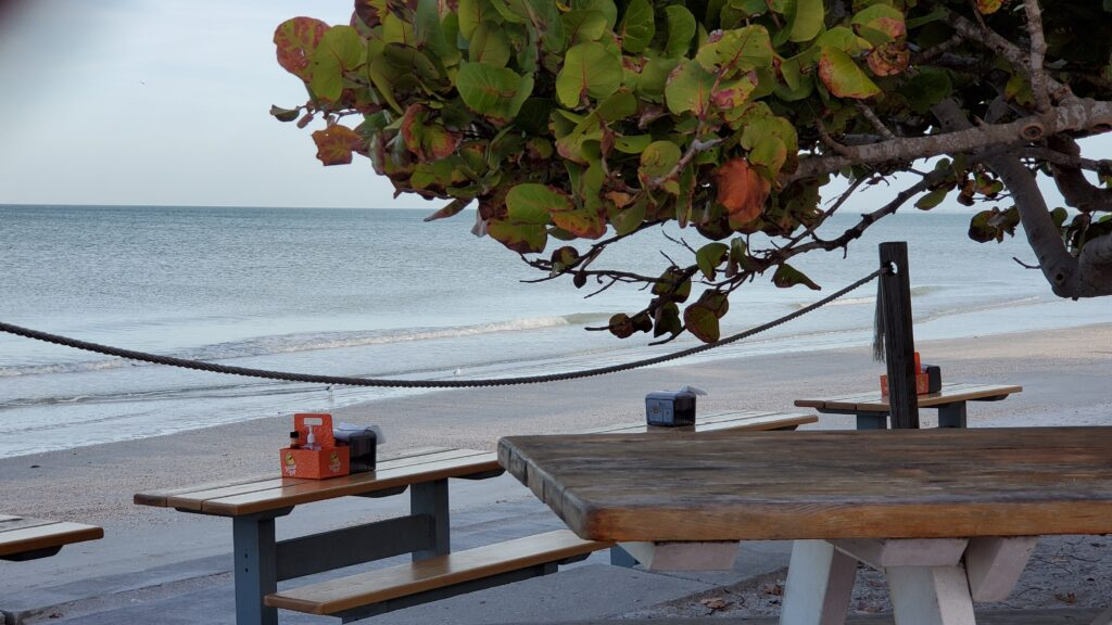 Picnic tables on the beach at Paradise Grill.
