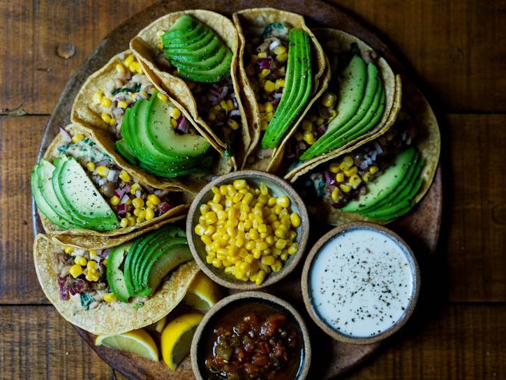 Platter of vegan tacos with corn, avocados, salsa, and dip