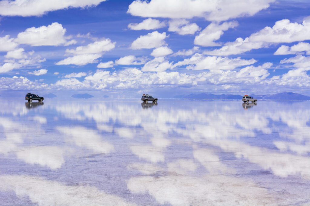 Reflections of clouds and cars at the Uyuni Salt Flats in Bolivia.