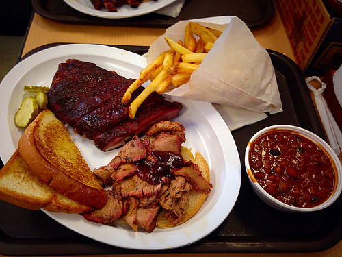 Ribs, chicken, toast, pickles, fries, chili, on a paper plate
