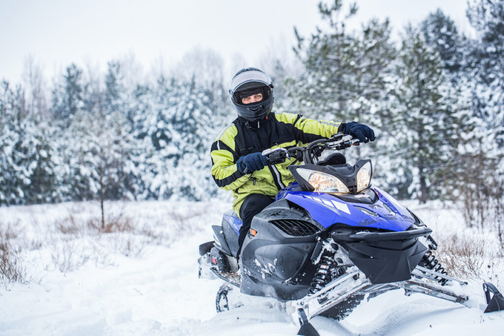 Riding a snowmobile during winter.