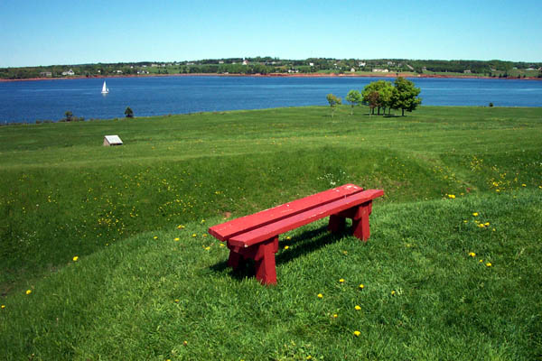 Rolling green hill and red bench